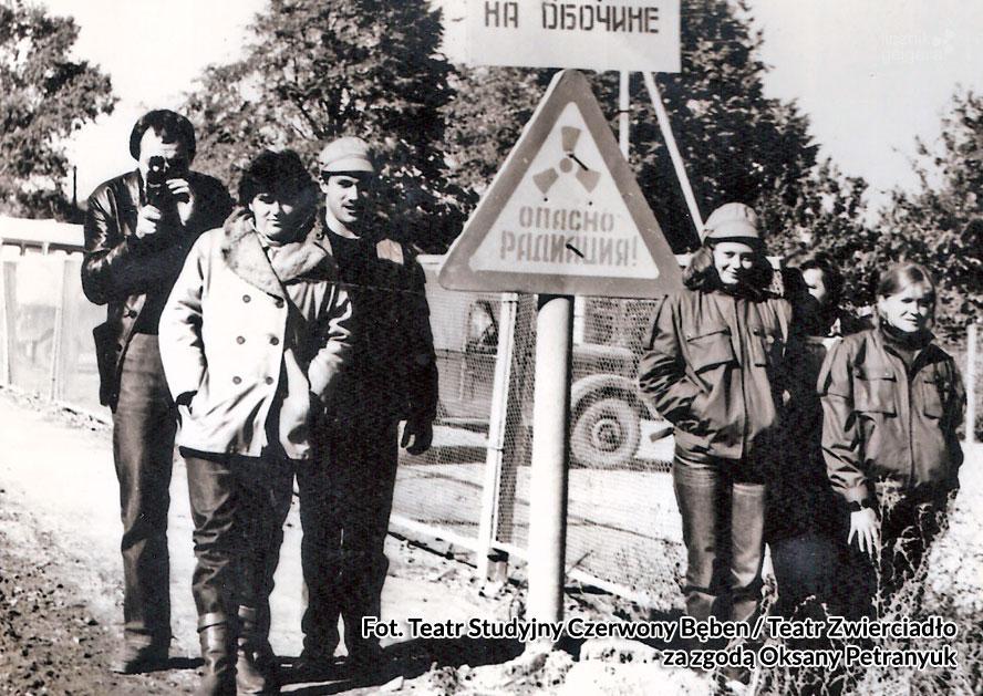 Grupa teatralna pozuje przed znakiem ostrzegającym przed promieniowaniem radioaktywnym. Fot. Teatr Studyjny Czerwony Bęben / Teatr Zwierciadło za zgodą Oksany Petranyuk