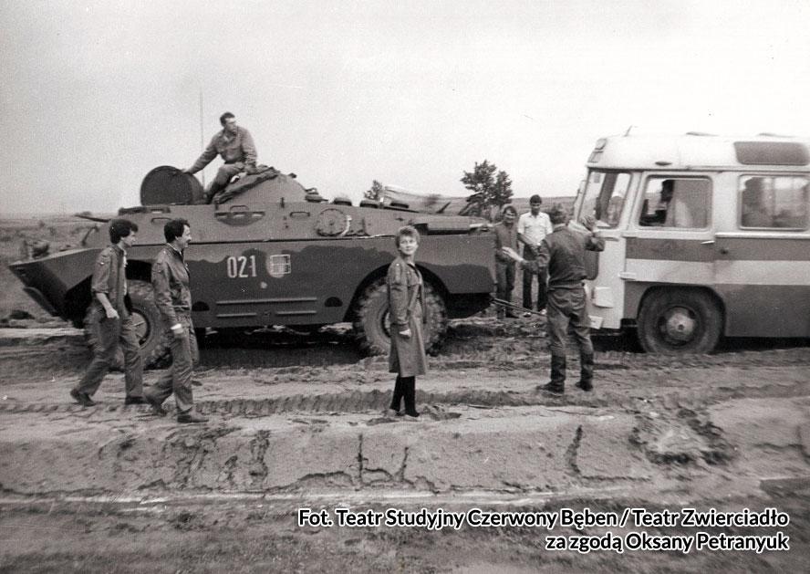 Wojskowi pomagają wyciągnąć zakopany w ziemi autobus grupy. Fot. Teatr Studyjny Czerwony Bęben / Teatr Zwierciadło za zgodą Oksany Petranyuk